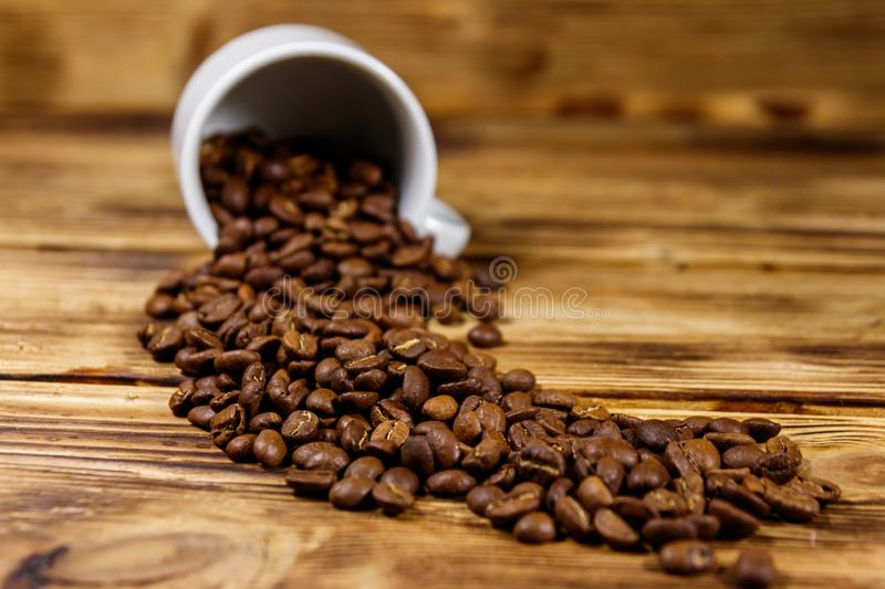 Roasted coffee beans spill out of cup on wooden table. Roasted coffee beans spill out of cup on a wooden table royalty free stock images