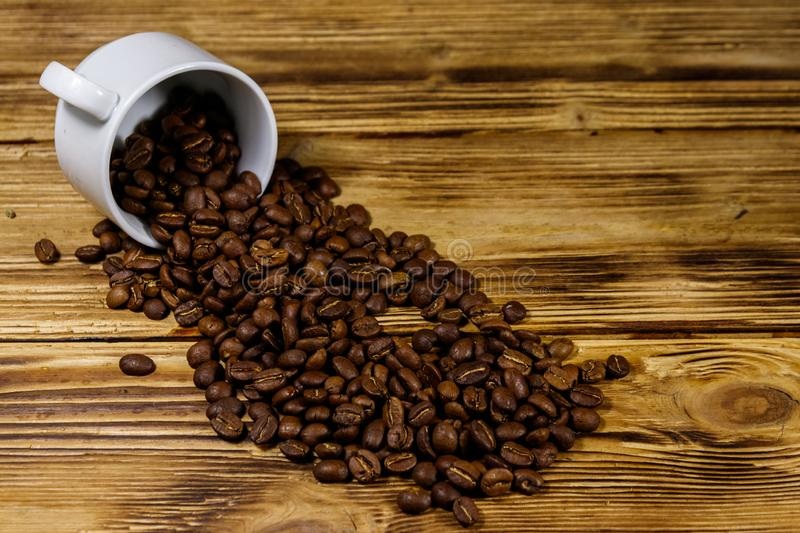 Roasted coffee beans spill out of cup on wooden table. Roasted coffee beans spill out of cup on a wooden table stock photo