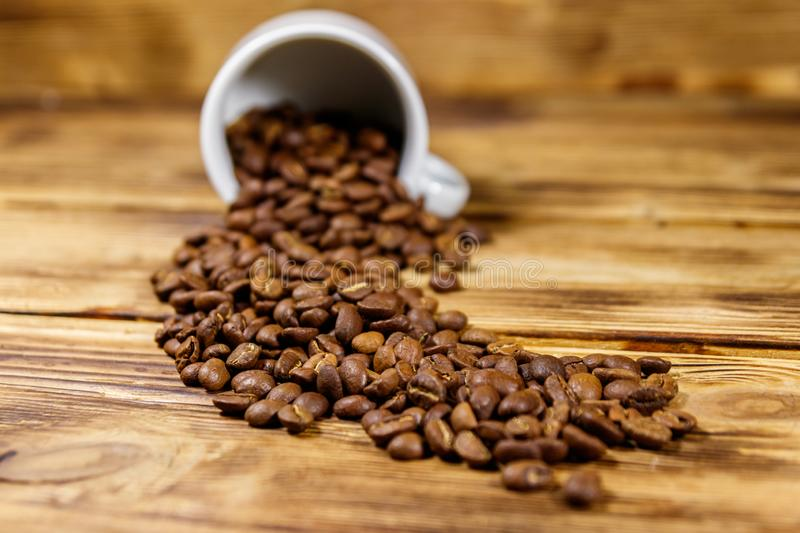Roasted coffee beans spill out of cup on wooden table. Roasted coffee beans spill out of cup on  a wooden table royalty free stock photo