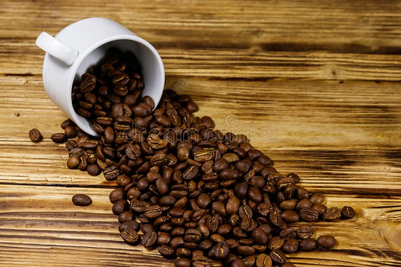 Roasted coffee beans spill out of cup on wooden table. Roasted coffee beans spill out of cup on a wooden table royalty free stock photos
