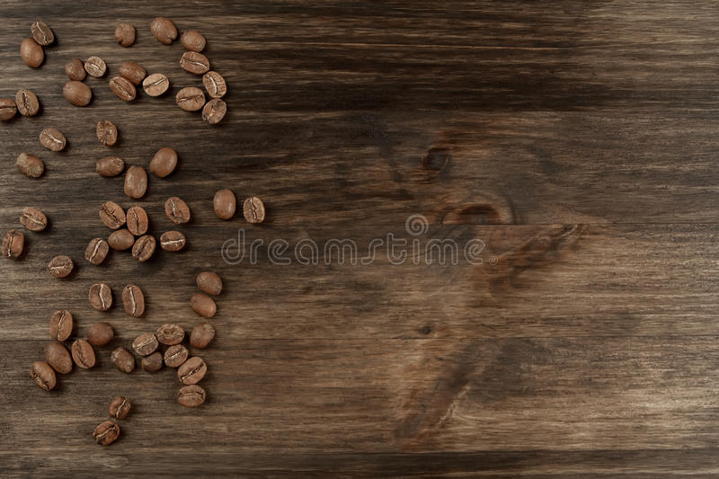 Roasted coffee beans in a spoon and cinnamon sticks on wooden background royalty free stock images