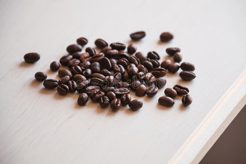 Roasted coffee beans are on white wooden desk stock images