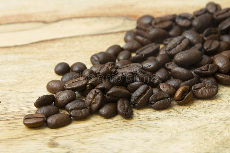 Roasted coffee beans on a wooden background espresso black. Roasted italian espressobeans on a wooden plate  as background whole beans royalty free stock image