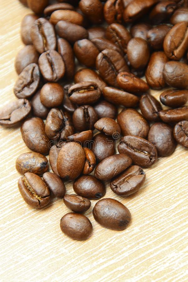Roasted coffee beans on a wooden background espresso black. Roasted italian coffee espressobeans on a wooden plate  as background whole beans royalty free stock photography