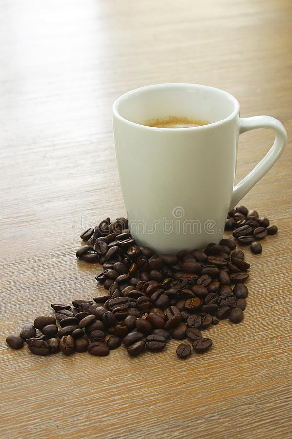 Roasted coffee beans on a wooden background espresso black. Roasted italian coffee espressobeans on a wooden plate  as background whole beans with a cup of royalty free stock photos