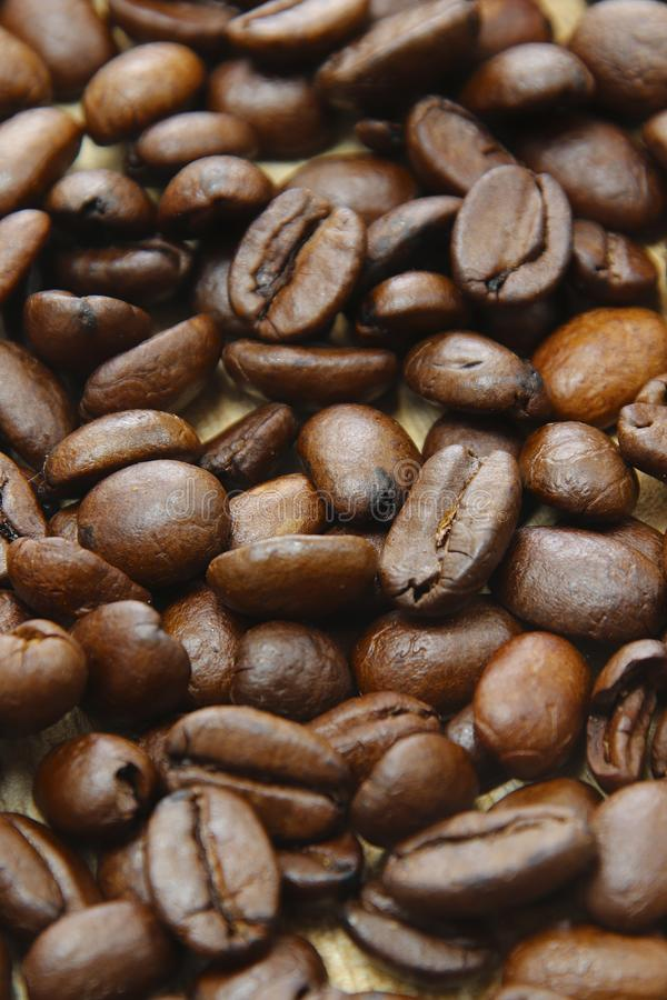 Roasted coffee beans on a wooden background espresso black. Roasted italian coffee espressobeans on a wooden plate  as background whole beans royalty free stock image
