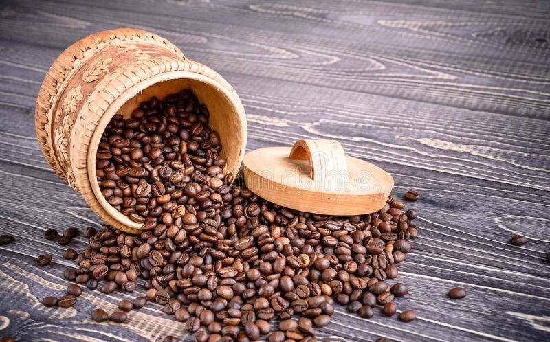 Roasted coffee beans in wooden basket on a wooden background stock photo