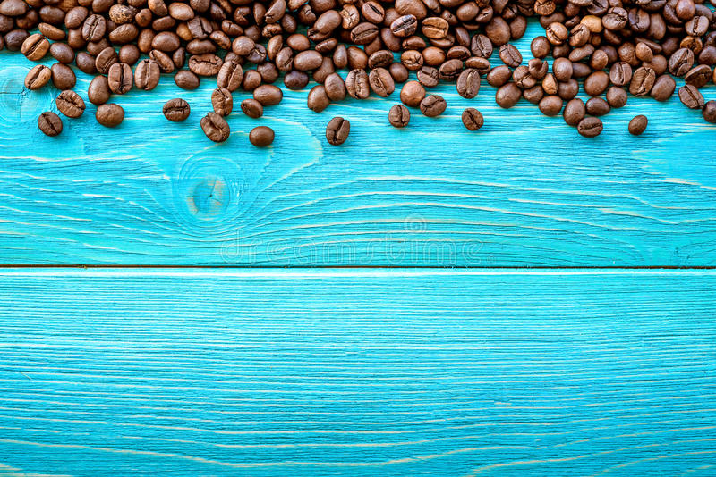 Roasted coffee beans in wooden basket on a wooden background royalty free stock photo