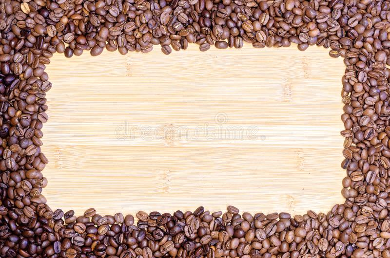 Roasted coffee beans on the wooden board. Roasted coffee beans lying on the wooden board with place for personal text royalty free stock images