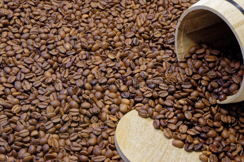 Roasted coffee beans and a wooden container. Wooden coffee container lying in the roasted coffee beans, in thd corner of the picture royalty free stock photography