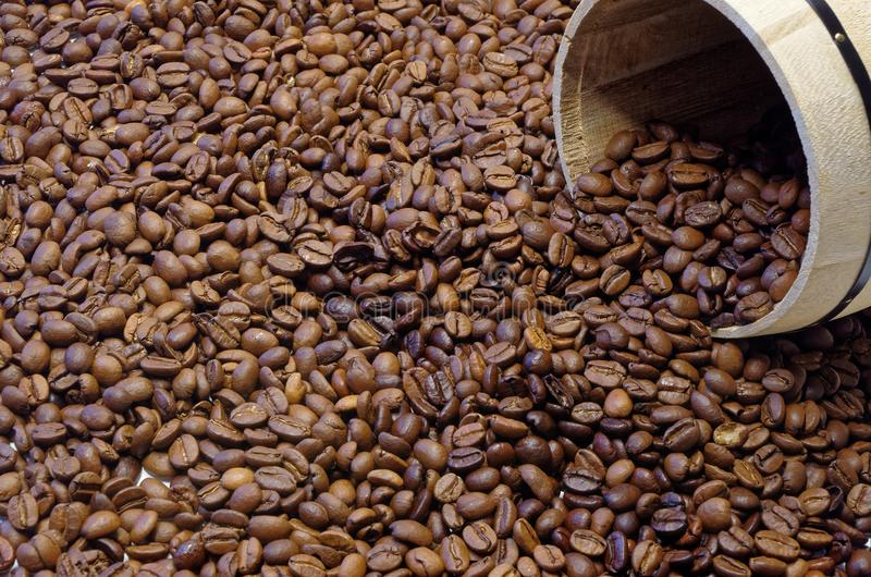 Roasted coffee beans and a wooden tin. Open wooden tin with coffee lies in roasted coffee beans as a background royalty free stock photos