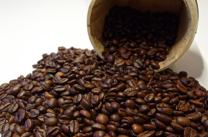 Roasted coffee beans and a wooden tin. On white background stock image