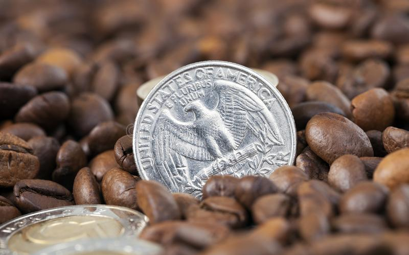 Roasted coffee, close-up. A large number of roasted grains of fresh coffee, closeup. on the grains are coins of different states, including a quarter of the royalty free stock photos