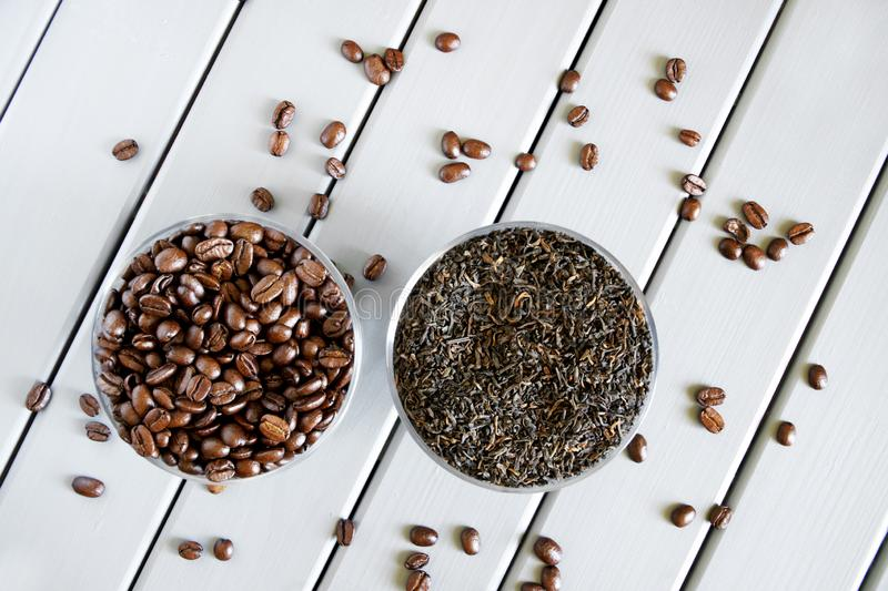 Roasted coffee grains and dried black tea on a wooden table. The problem of choosing a drink. Daylight royalty free stock images
