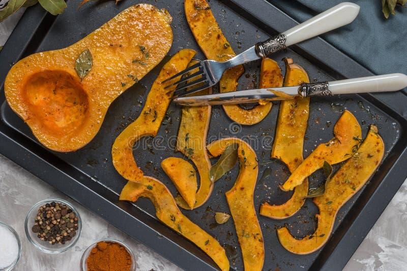 Roasted cortou a polpa de butternut temperado com sal, pimenta doce, pimenta e tomilho no prato cozido fotografia de stock