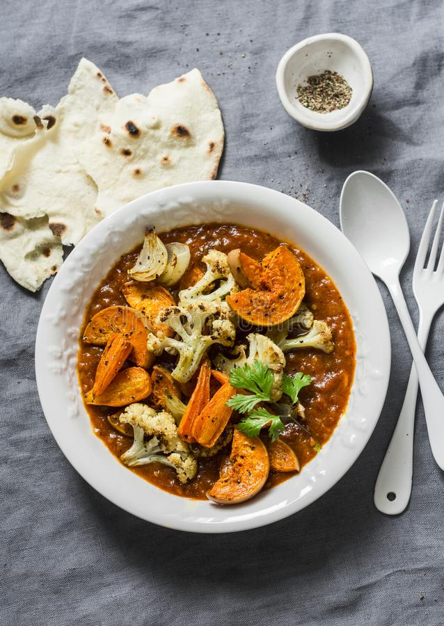 Roasted curry vegetables. Sweet potatoes, cauliflower, carrots, onions, pumpkin with curry sauce on grey background, top view royalty free stock photography
