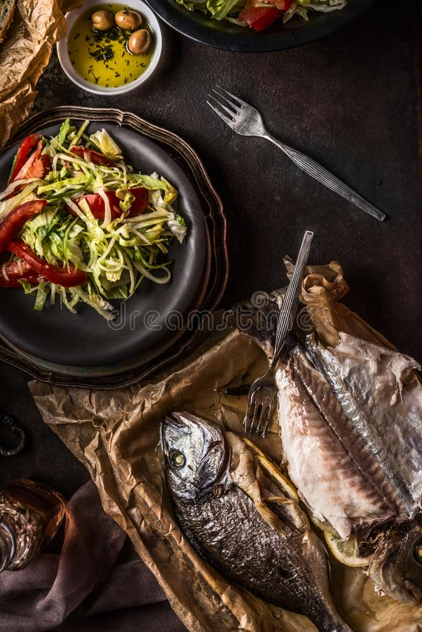 Roasted dorado fishes on dark rustic kitchen table background with fresh salad , olives oil and fork, top view. Healthy lunch. Concept. Mediterranean food royalty free stock photos