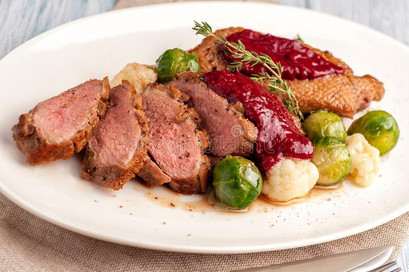 Roasted duck breast with vegetable garnish royalty free stock images