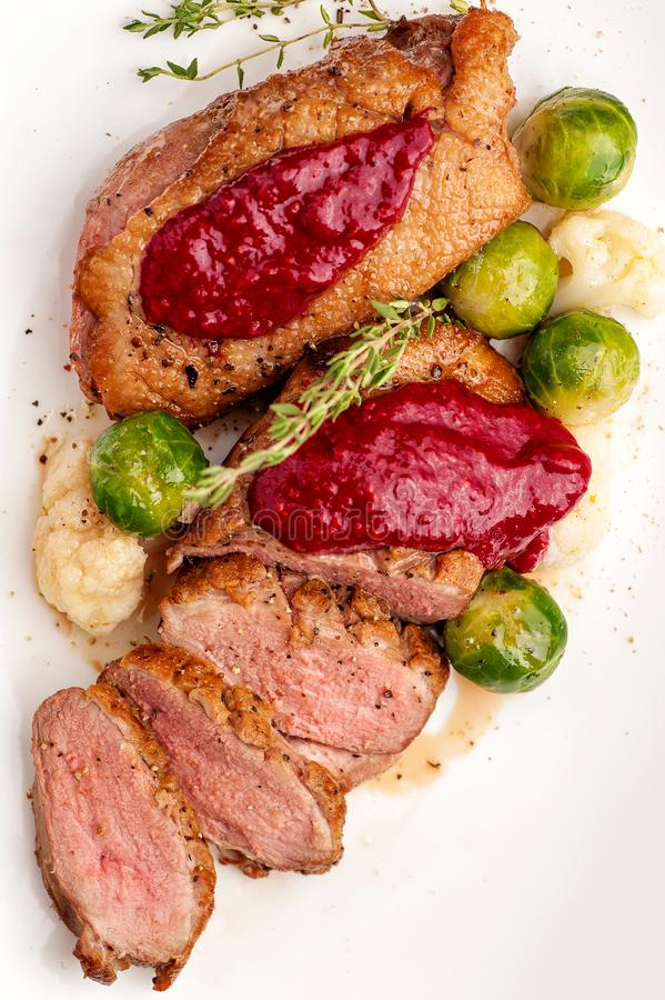 Roasted duck breast with vegetable garnish. royalty free stock photo