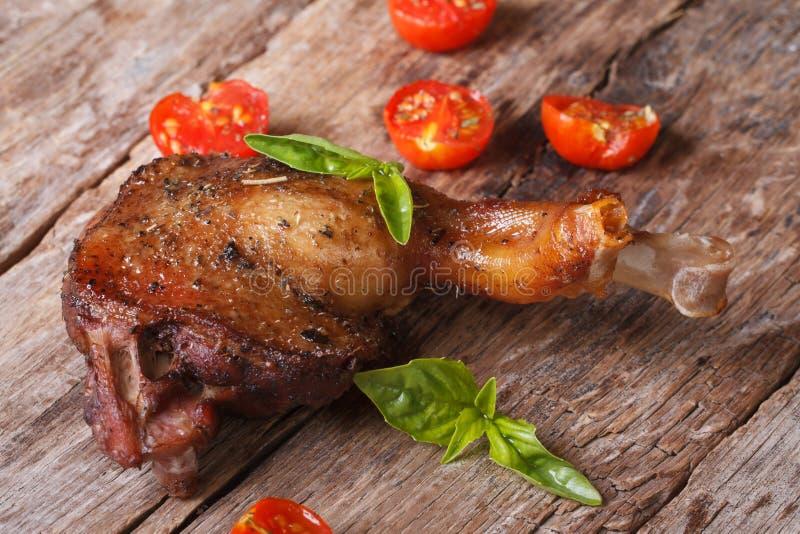 Roasted duck leg with basil and cherry tomatoes horizontal. Roasted duck leg with basil and cherry tomatoes close up on an old table horizontal stock photos