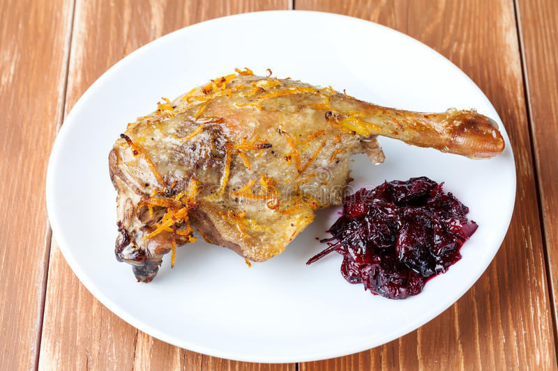 Roasted duck leg with cherry sauce. Roasted duck with cherry sauce on white plate stock image