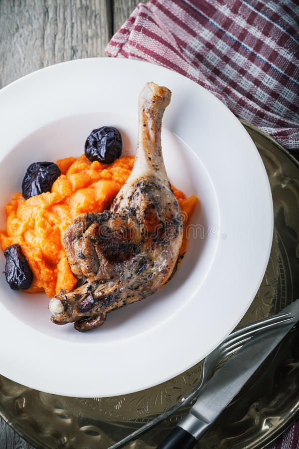 Roasted duck leg with mashed carrot and dried prunes.  royalty free stock photography