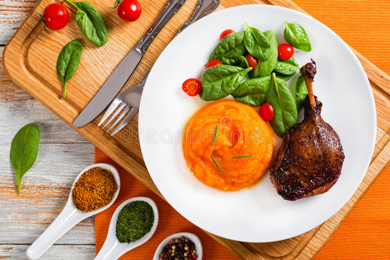Roasted duck leg with mashed pumpkin and salad stock photography