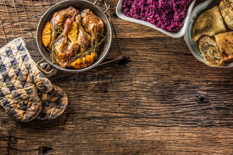 Roasted duck legs in pan with oranges herbs red cabbage and potato pankaces.  stock photography