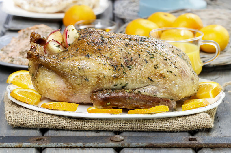 Roasted duck with oranges on wooden table