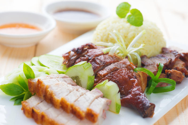 Roasted duck, roasted pork crispy siu yuk and Charsiu. Chinese style, served with steamed rice on dining table. Singapore cuisine royalty free stock photography
