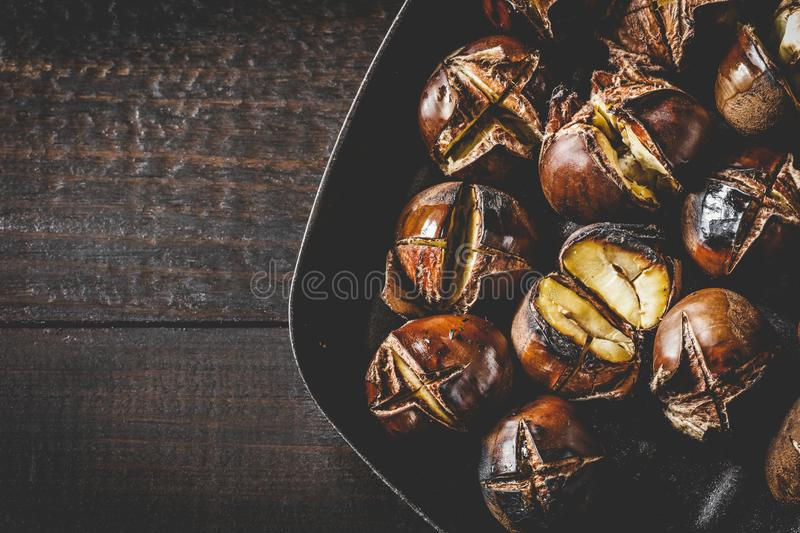 Roasted edible chestnuts in cast iron skillet over rustic wooden table royalty free stock image