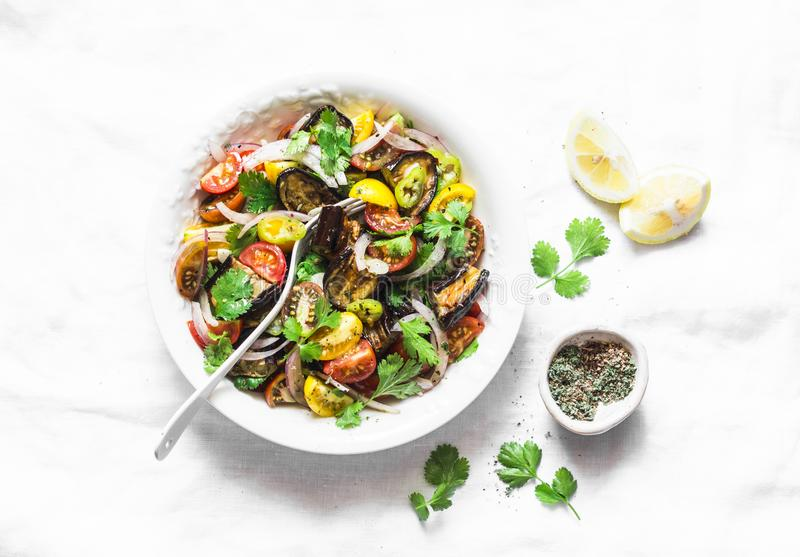 Roasted eggplant, sweet tomato and cilantro mediterranean style salad on light background, top view. Vegetarian food. Concept stock images