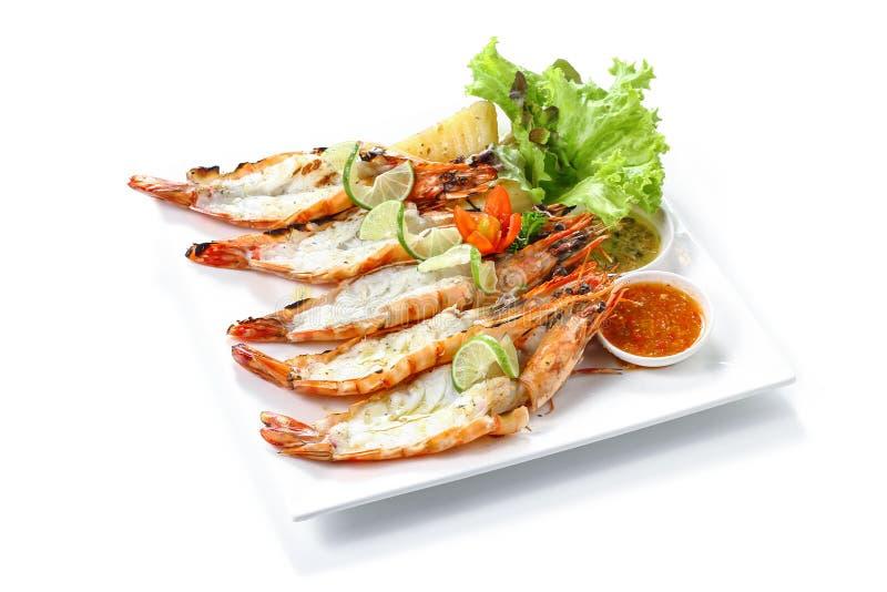Roasted a fendu les crevettes roses noires de tigre avec les pommes vapeur, la tranche de chaux, les légumes frais et la sauce à  photo libre de droits