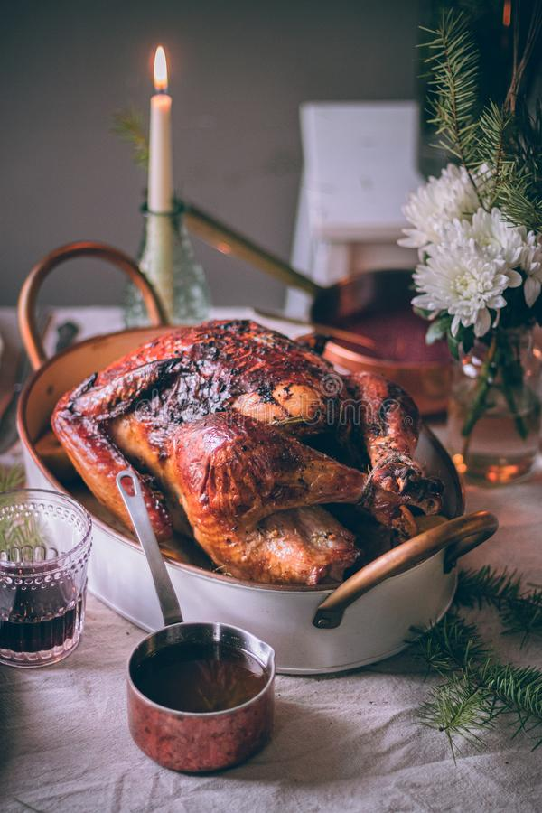 Roasted festive Thanksgiving Day turkey on festive table setting. Family celebration. Thanksgiving day in November. Roasted. Poultry in deep white baking dish royalty free stock image