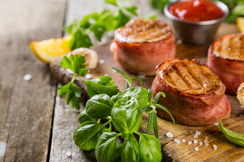 Roasted filet mignon with herbs and spices. Rustic wood background stock photography