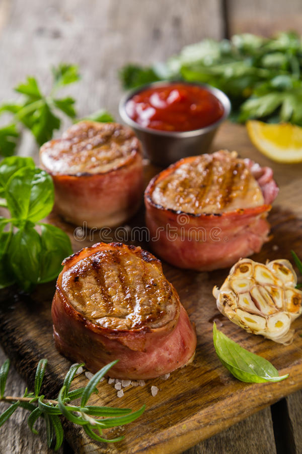 Roasted filet mignon with herbs and spices. Rustic wood background royalty free stock photos