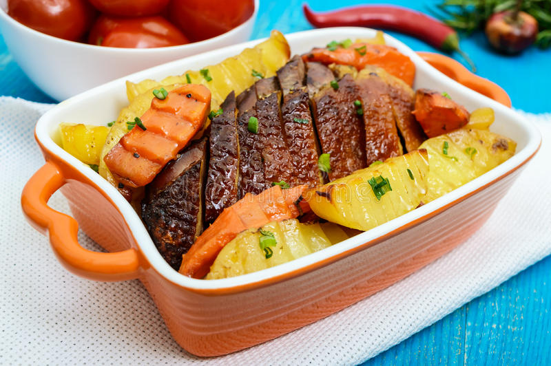 Roasted fillet of brisket goose, sliced, potatoes rustic in a ceramic bowl with marinated tomatoes royalty free stock photo