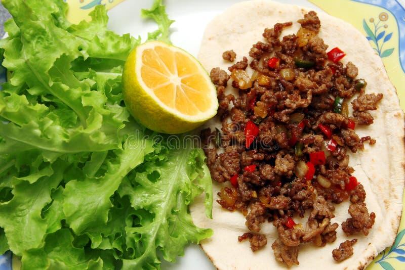 Roasted finhackade nötkött med chilipeppar på tortillan med grönsallat och citronen arkivbild