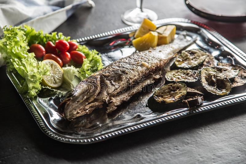 Roasted fish on dish with fresh and grilled vegetable.  royalty free stock images