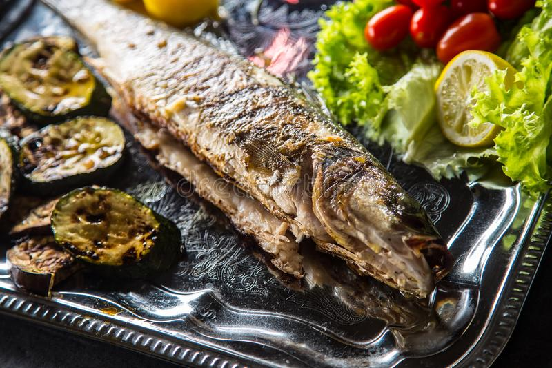 Roasted fish on dish with fresh and grilled vegetable.  stock image