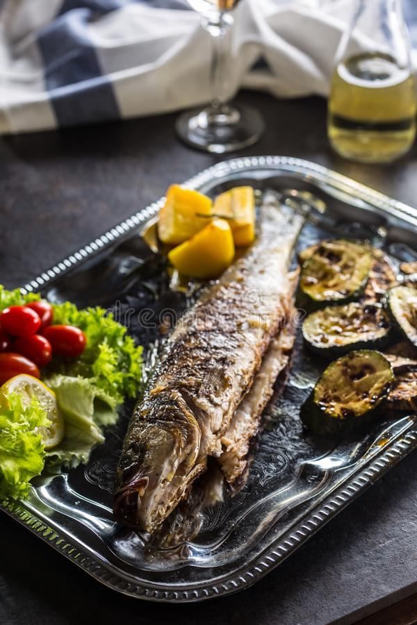 Roasted fish on dish with fresh and grilled vegetable.  royalty free stock photo