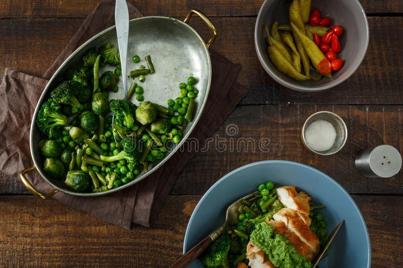 Roasted French bean, Brussels sprouts, green peas, chicken breast. Roasted French bean, Brussels sprouts, green peas and chicken breast on a dark wooden stock images