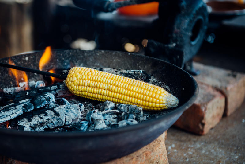 Roasted fresh corn cob. A tender corncob is roasted on a fire in road side food stall in India. A popular roadside food during rainy season stock photography