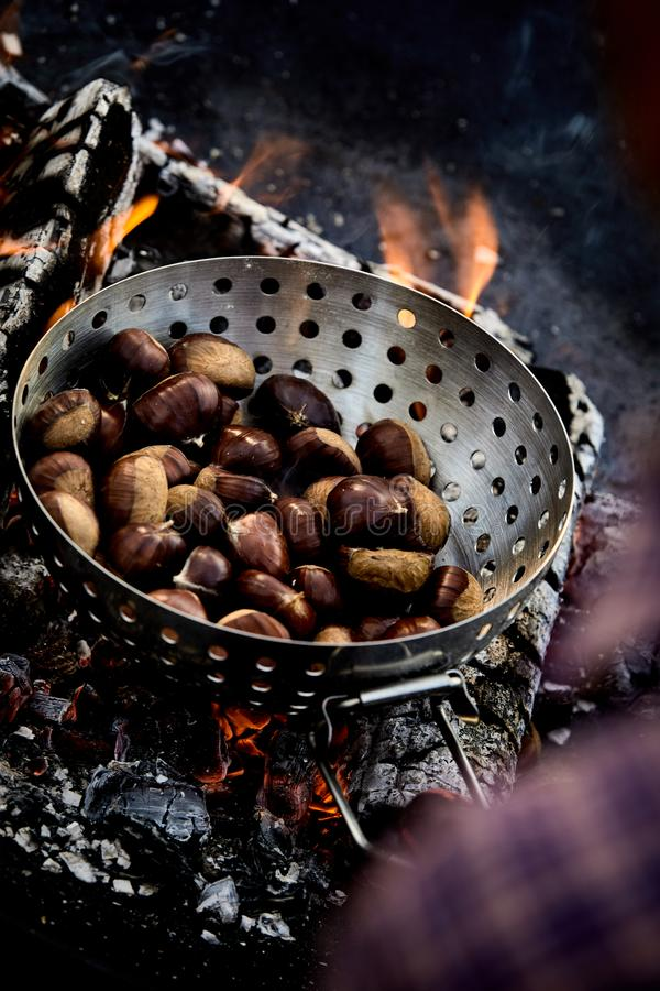 Roasted fresh sweet chestnuts on hot coals stock photos