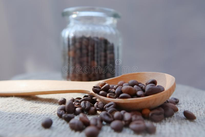 Roasted grains of natural aromatic coffee. Scattered from a glass jar over a piece of coarse cloth lying on a wooden table stock images