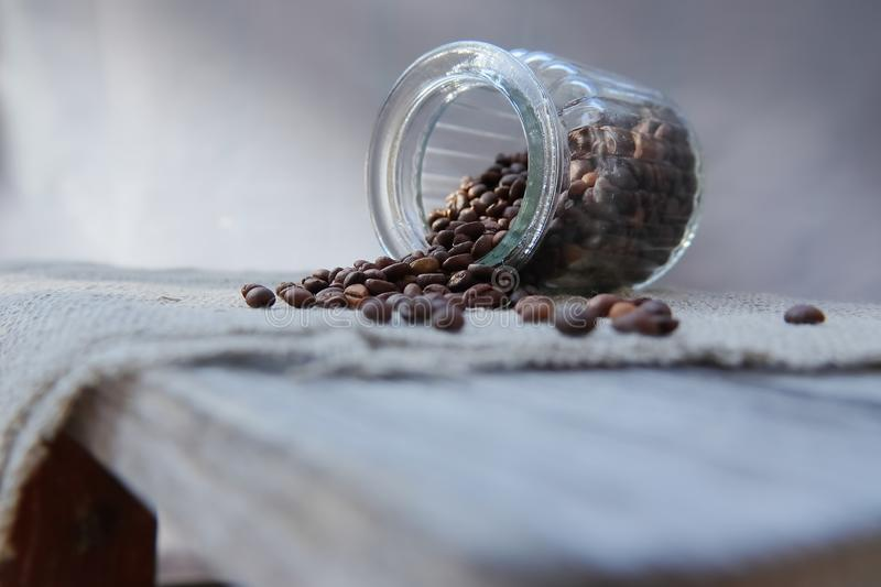 Roasted grains of natural aromatic coffee. Scattered from a glass jar over a piece of coarse cloth lying on a wooden table royalty free stock image