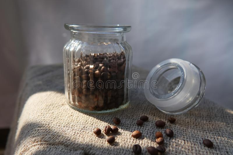 Roasted grains of natural aromatic coffee. Scattered from a glass jar over a piece of coarse cloth lying on a wooden table royalty free stock images