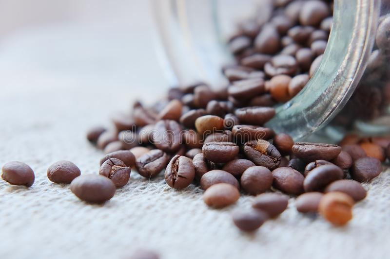 Roasted grains of natural aromatic coffee. Scattered from a glass jar over a piece of coarse cloth lying on a wooden table stock photography