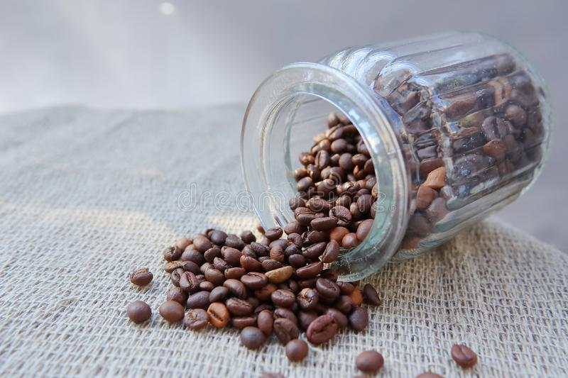 Roasted grains of natural aromatic coffee. Scattered from a glass jar over a piece of coarse cloth lying on a wooden table stock photo