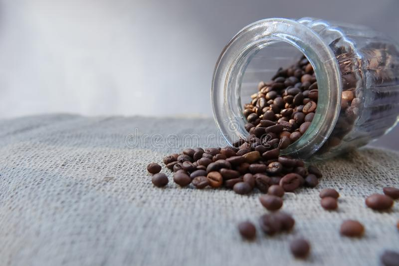 Roasted grains of natural aromatic coffee. Scattered from a glass jar over a piece of coarse cloth lying on a wooden table stock image